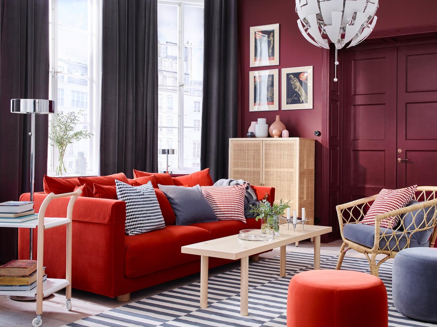 Harmaa ja tummanpunainen olohuone, jossa oranssi sohva, raidallinen matto ja rottinkituoli.