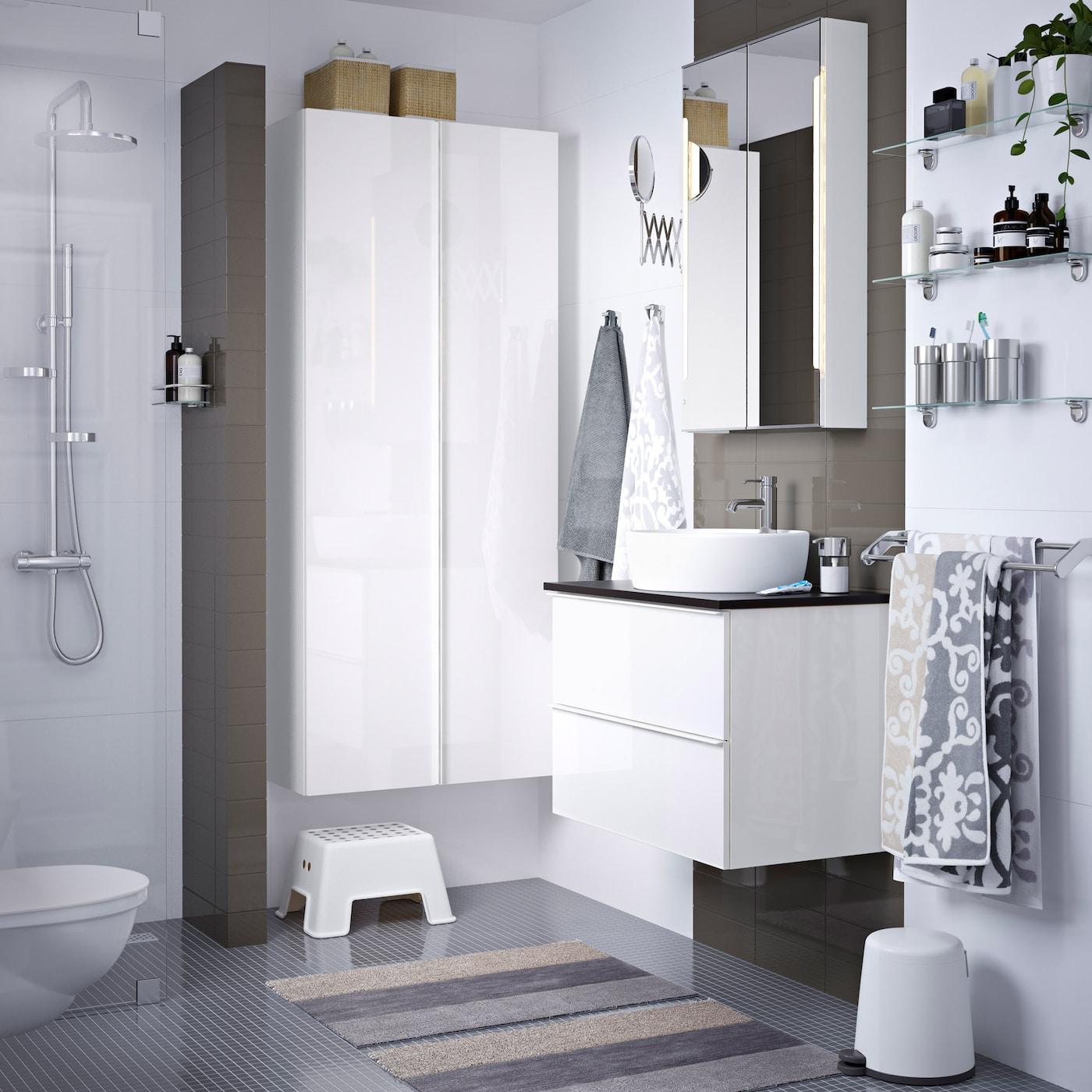 Harmaa ja valkoinen kylpyhuone, jossa valkoinen allaskaluste ja kaappi.