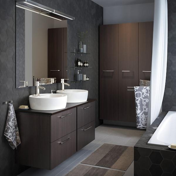 Harmaa kylpyhuone, jonka mustanruskeissa seinäkaapeissa on kromatut vetimet. Kauniit malja-altaat kruunaavat tyylin.