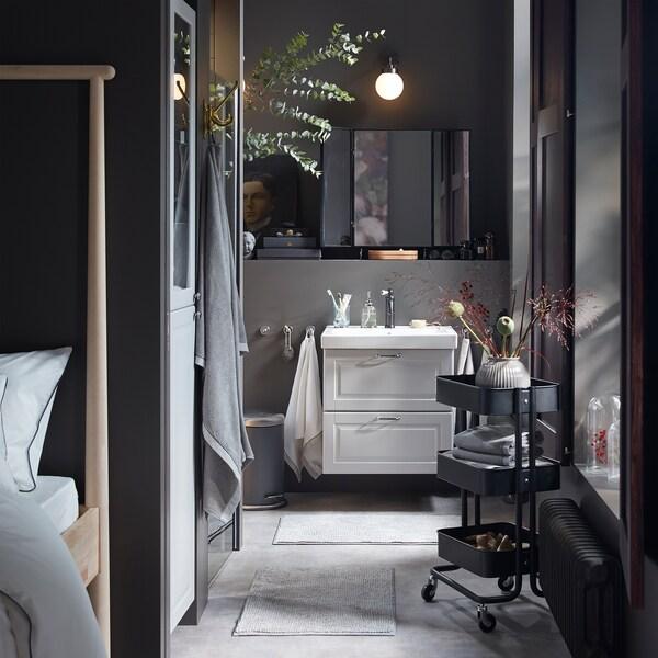Harmaa kylpyhuone, pesuallas ja vaaleanharmaa korkea kaappi, musta tarjoiluvaunu ja kuivakukkia.