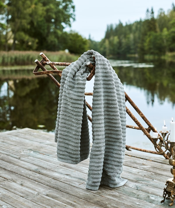 Harmaa, pehmeä pyyhe on ripustttu roikkumaan ruosteisista tikkaista laiturin nokassa. Taustalla tyyni järvimaisema.