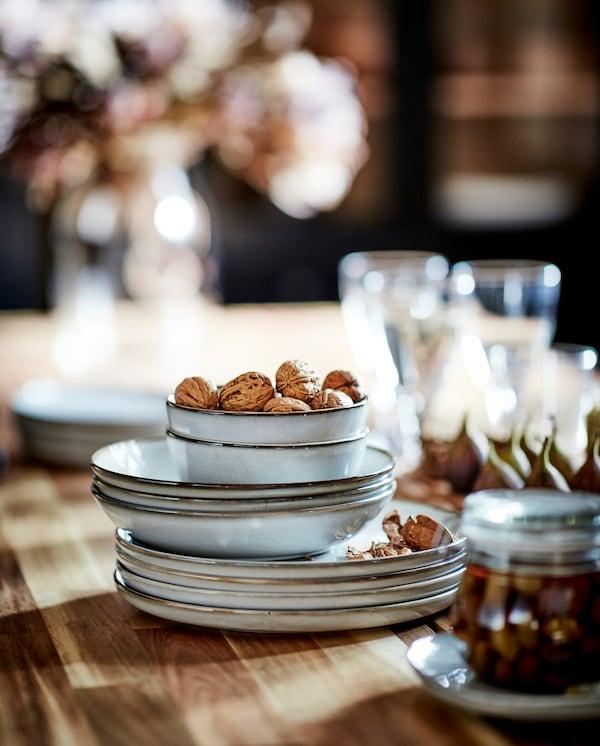 Harmaat, hiekkalasitetut lautaset ja kulhot tummilla, koristeellisilla reunoilla on katettu akaasia pöydälle. Ylimmässä kulhossa on saksanpähkinöitä.