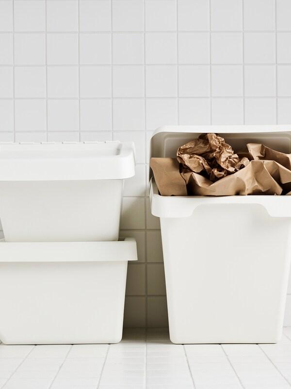 Három fehér SORTERA tartály egy fehérrel csempézett helyiségben, az egyik tartályban pedig barna papírhulladék látható.