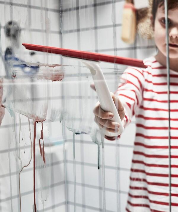 Haurra kamiseta marradunarekin, dutxa lehorrean sartuta; beirak garbitzekoa erabiltzen ari da dutxako itxiturako akuarelak garbitzeko.
