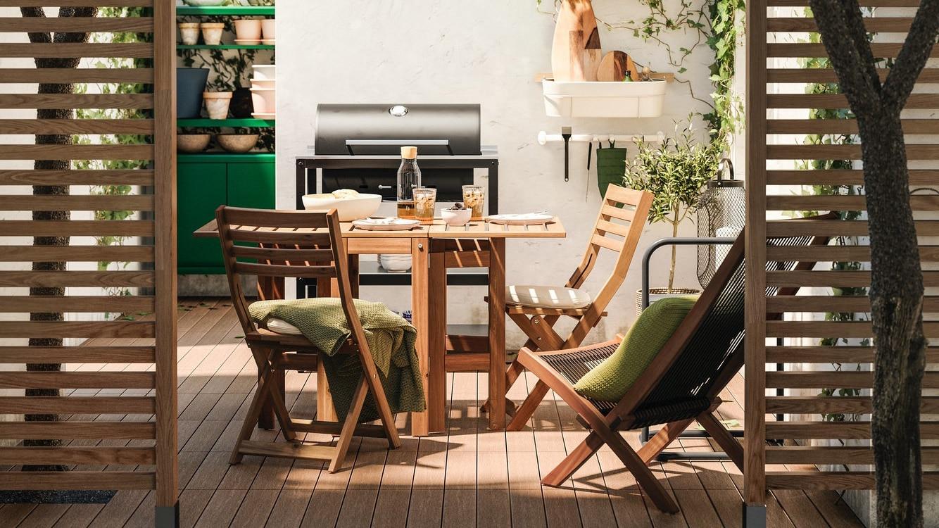 Havebord med tilhørende stole af træ står på en træterrasse.