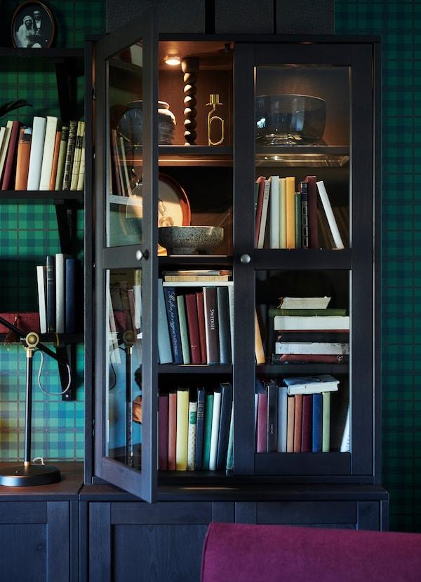 HAVSTA خزانة تخزين من ايكيا لون بني داكن مع أرفف زجاجية وإضاءة مدمجة، حيث تم تركب باب واحد مفتوحاً لإظهار الكتب والمزهريات في الداخل.