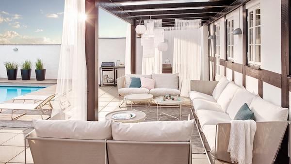 HAVSTEN serien med hvide sidde- og hvilemøbler står under et halvtag ved siden af en swimmingpool.