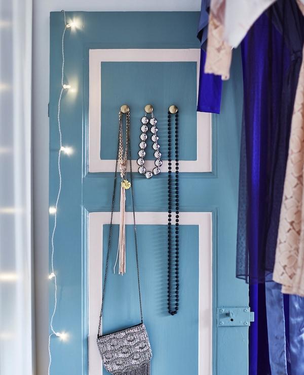 Hay una antigua puerta de madera pintada de azul claro y blanco, a la que han añadido manillas para colgar pañuelos y un bolso.