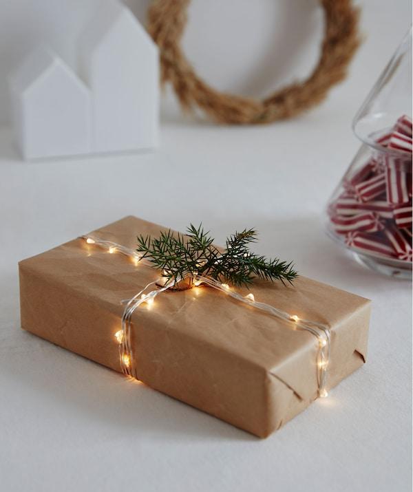 هدية مستطيلة ملفوفة بورق بني مع سلسلة إضاءة رقيقة مضاءة بدل الخيط؛ وغصين مثل شجرة التنوب للزينة.