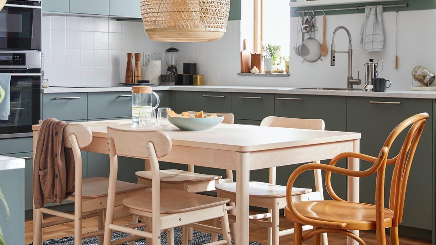 Heller Essbereich in einer Küche mit Lebensmitteln in einer Schüssel und einem Krug am Tisch.