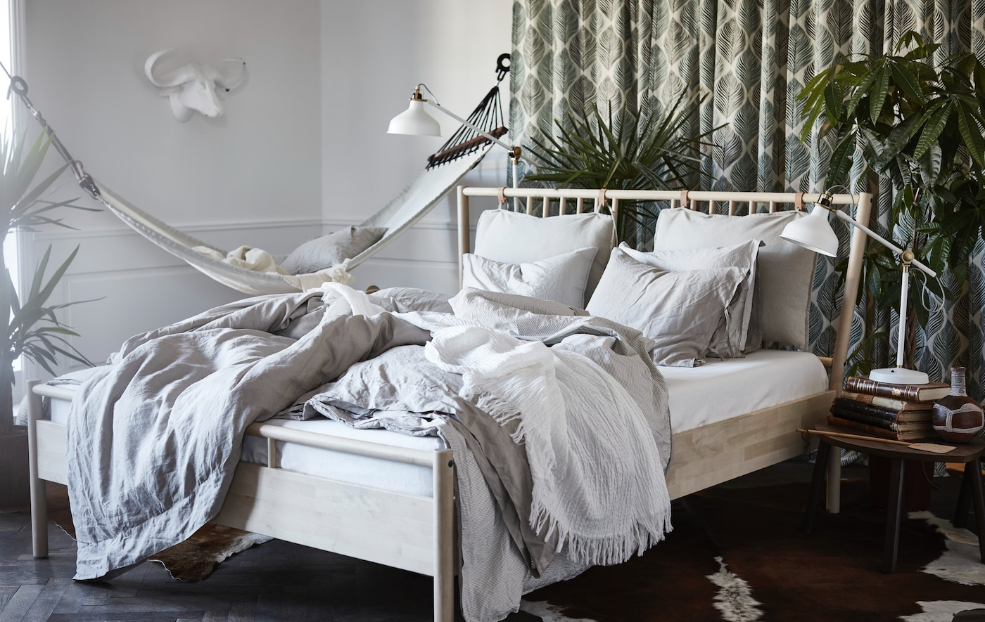 Helles Schlafzimmer mit BJÖRKSNÄS Bettgestell in Birke und einer weißen Hängematte.