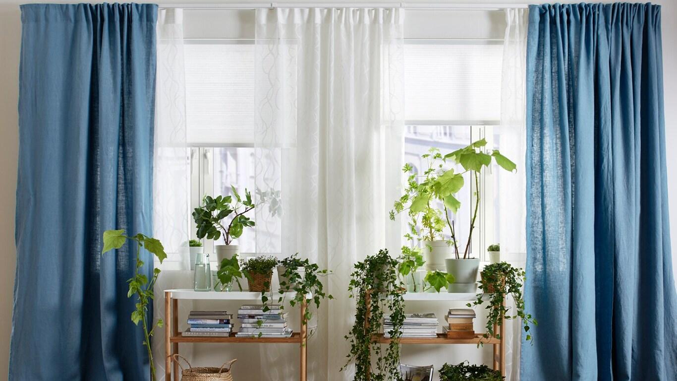 Helles Wohnzimmer mit Doppelfenster, eingerichtet mit blauem AINA Gardinenpaar & weißer HOPPVALS Wabenjalousie