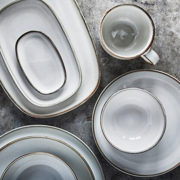 Hellgraue Schüsseln, Teller und Serviergeschirr stehen zusammen mit einem Becher auf einer grauen Oberfläche.