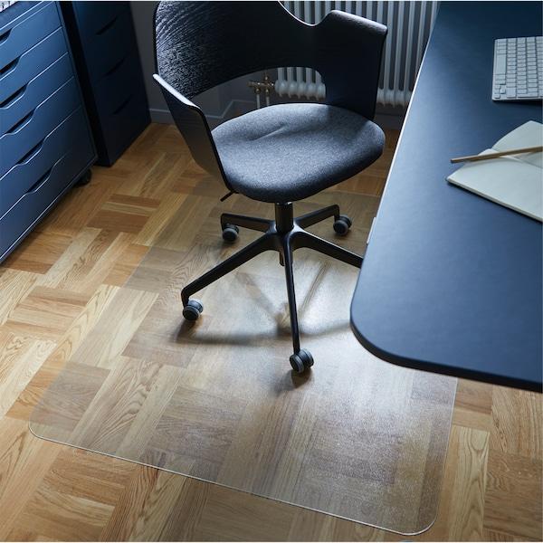 Hemmakontor med ett transparent KOLON golvskydd som skyddar golvet under en konferensstol som är placerad bredvid ett skrivbord.