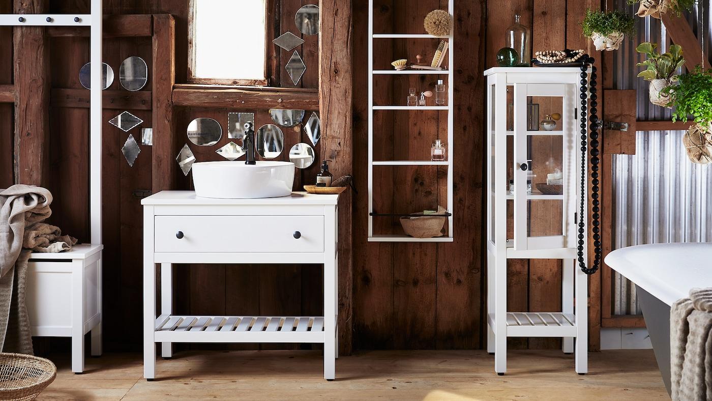 ห้องน้ำที่มีผนังไม้สีเข้มตกแต่งด้วยกระจกเงาเล็ก ๆ รูปทรงแปลกตาหลายบาน และเฟอร์นิเจอร์ห้องน้ำ HEMNES/เฮมเนส สีขาว