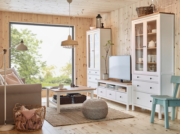 HEMNES møbelserie af fyr omfatter høje vitrineskabe, et sofabord og et tv-bord fremstillet af frisk, glat fyrretræ.