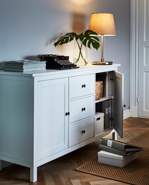 HEMNES sideboard with a lamp and various showpieces on top. A door ajar reveals boxes and binders stored within.