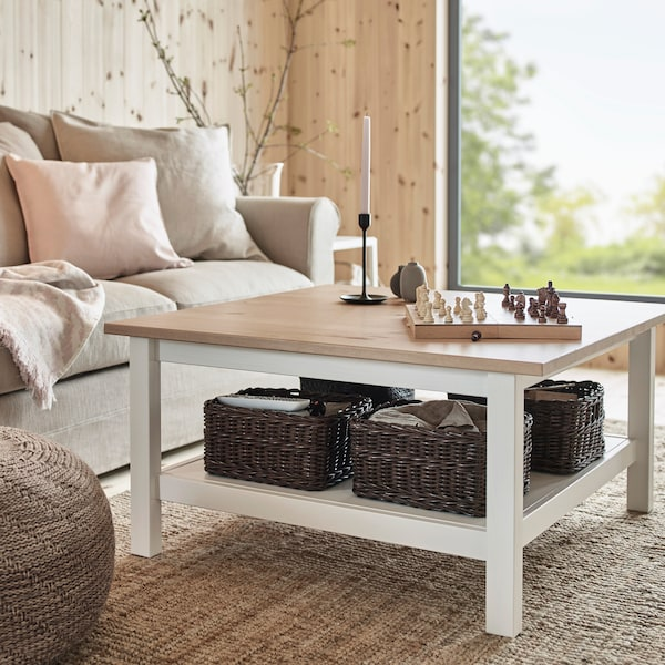 HEMNES sofabord med mørkebrune, vævede kurve på en hvid hylde under bordet.