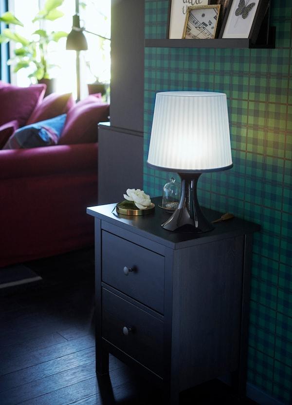HEMNES طاولة سرير جانبية من ايكيا باللون الأسود والبني تستخدم في مدخل مساحة صغيرة للجلوس، مع مصباح طاولة موضوعاً فوقها.