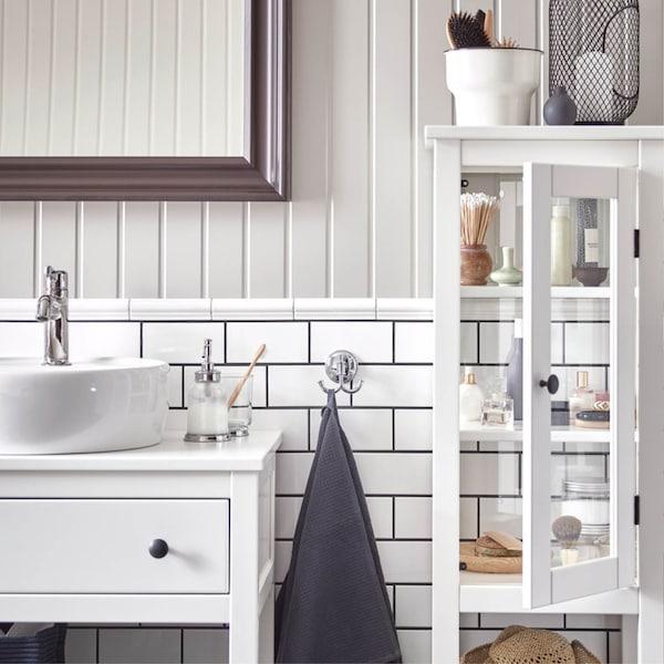 HEMNES witte badkamerkast met lade en lavabo naast een open witte HEMNES vitrinekast in een badkamer met metrotegels en witte lambrisering
