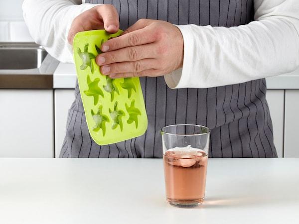 Hender som løsner isbiter fra PLASTIS isterningsbrett og putter i glass