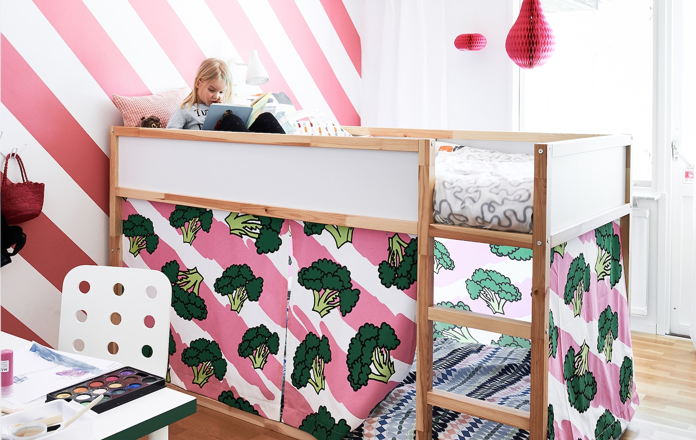 Henrik's daughter on her top bunk, reading a book against a white and bright pink striped wall in her redecorated bedroom.
