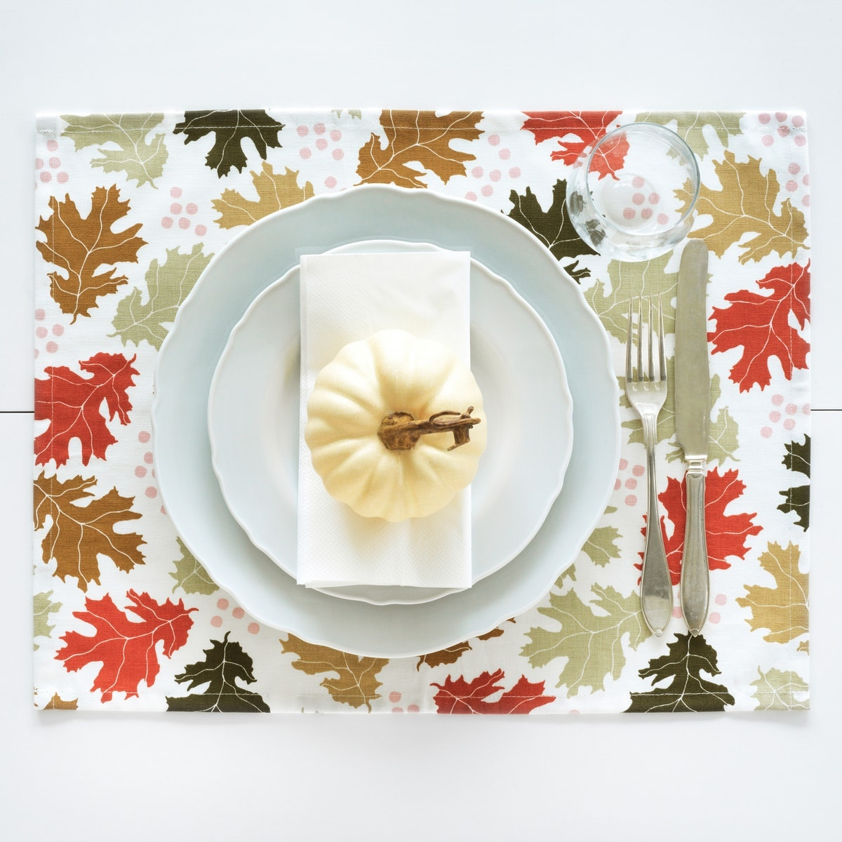 Herbstliche Tischdekoration mit Blätterplatzset und Zierkürbis