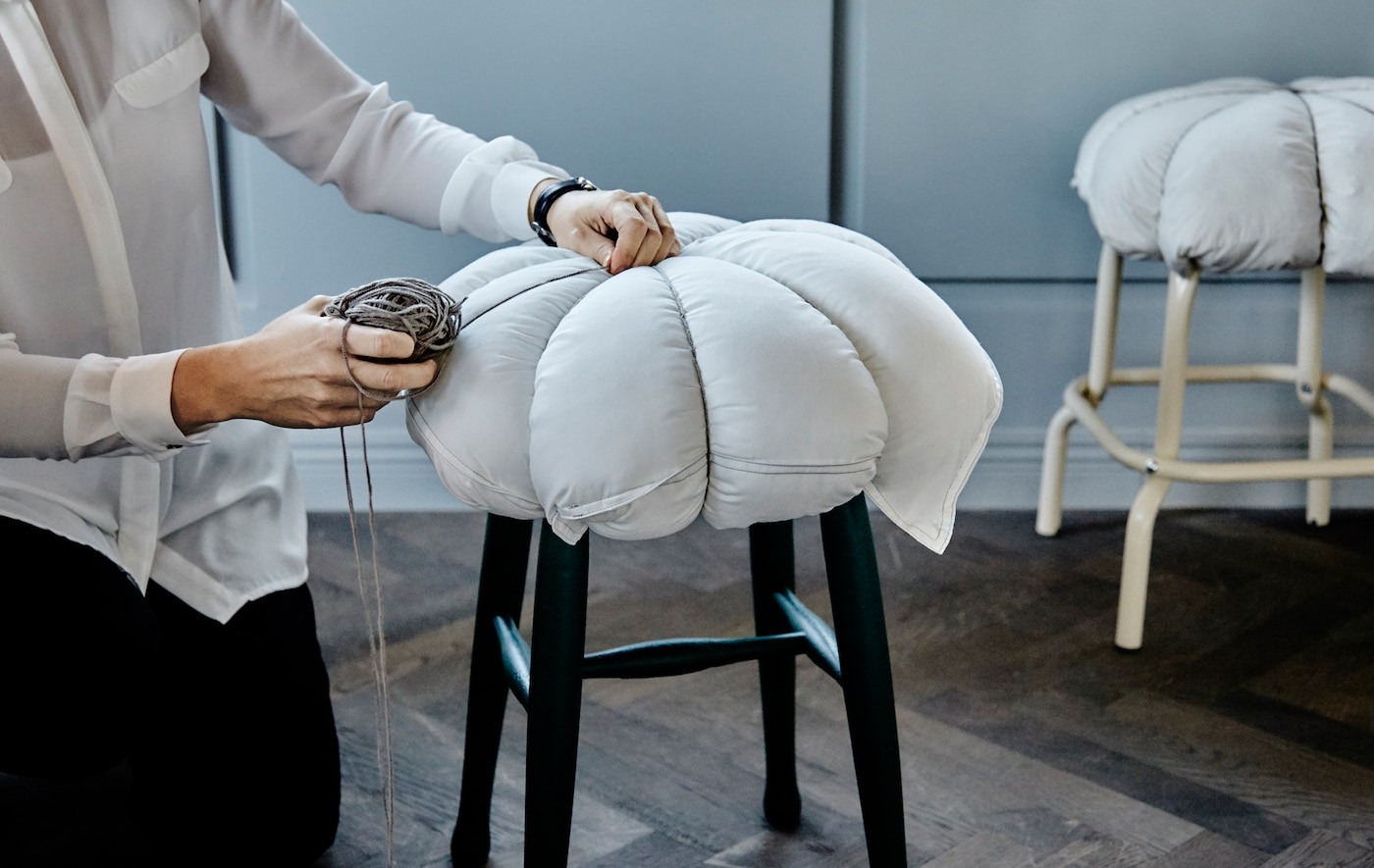 Here's a DIY idea that takes 5 minutes to put together and makes hard seats seriously comfy. All you need is a pillow and a length of string (we like the rustic twine version). Then loop your string over the pillow and stool making 8 equal sections and tie a firm knot at the top. Finished!