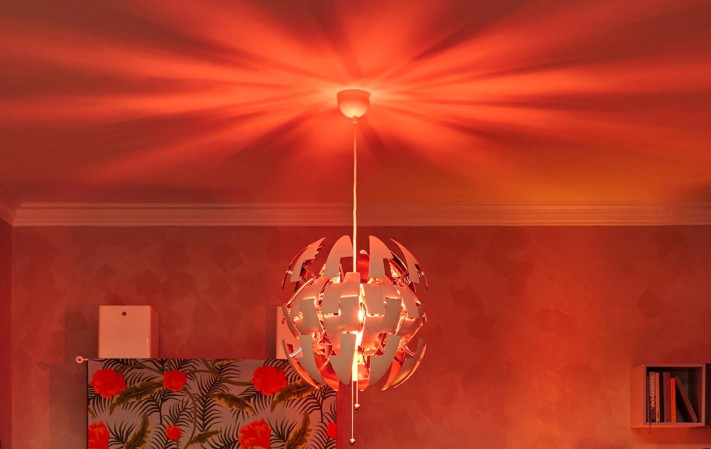 Het bovenste deel van een woonkamer, gedomineerd door een IKEA PS hanglamp. Het plafond weerkaatst een roodachtig licht en schept een echt clubgevoel.