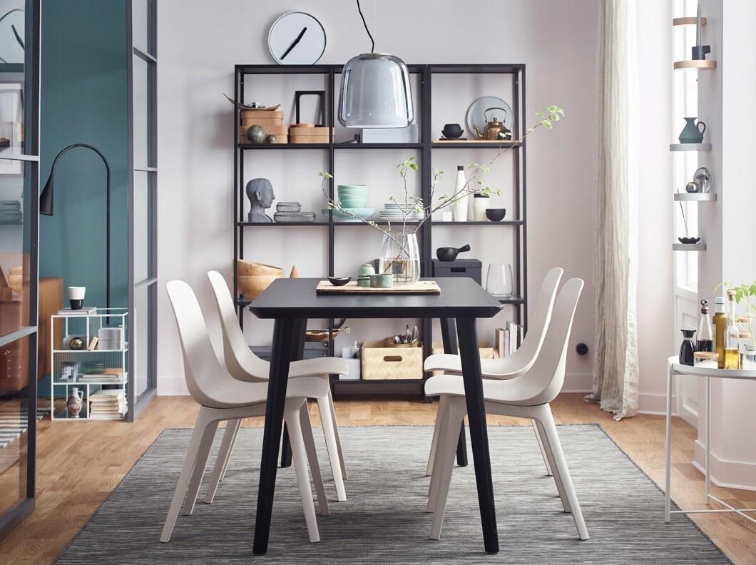 Het geheim van een stijlvolle eetkamer? Ontwerp pictogrammen zoals de bekroonde witte gerecycleerde stoelen van IKEA ODGER en een gedurfde zwarte LISABO-tafel.