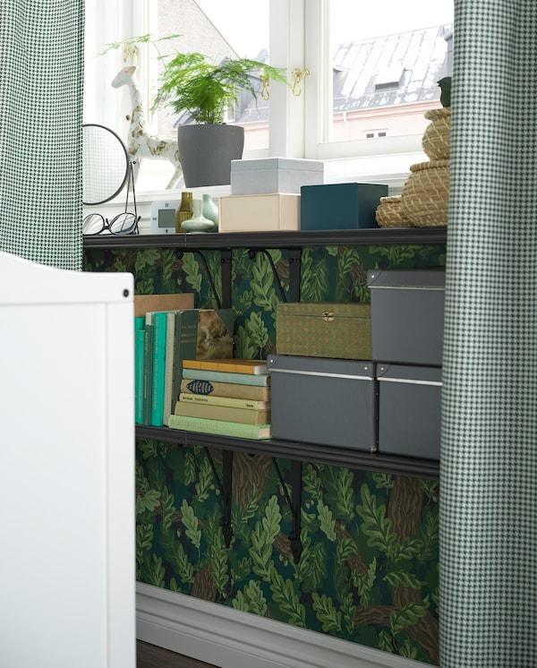 Hier sind zwei BERGSHULT/KROKSHULT Wandregale unter einem Fenster montiert zu sehen. Auf den Regalen stehen Bücher und Kästen.