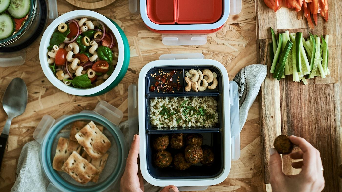 Hier werden Speisen in Lunchboxen gepackt. Eine von ihnen hat unterschiedliche Fächer für verschiedene Lebensmittel, in einem runden Behälter hingegen ist Nudelsalat zu sehen.