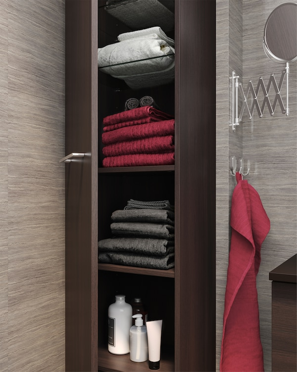 High cabinet in black-brown that's open to show spacious storage for towels, shampoos and more on glass- and wooden shelves.