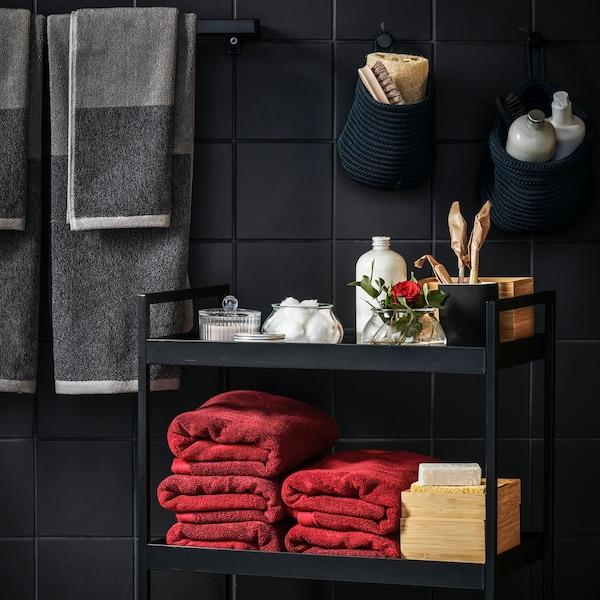 HIMLEÅN dark red marled bath towels neatly folded on bathroom cart in dark and moody bathroom setting