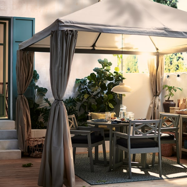 HIMMELSÖ paviljong på en solig och lummig terrass med grått BONDHOLMEN bord och stolar där det är uppdukat för en mysig måltid.