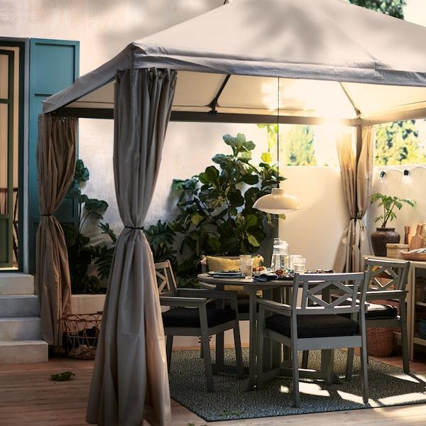 HIMMELSÖ pavilon egy napfényes és dús növényzetű kerti teraszon, egy meghitt étkezésre kész szürke BONDHOLMEN asztallal, alatta székekkel.