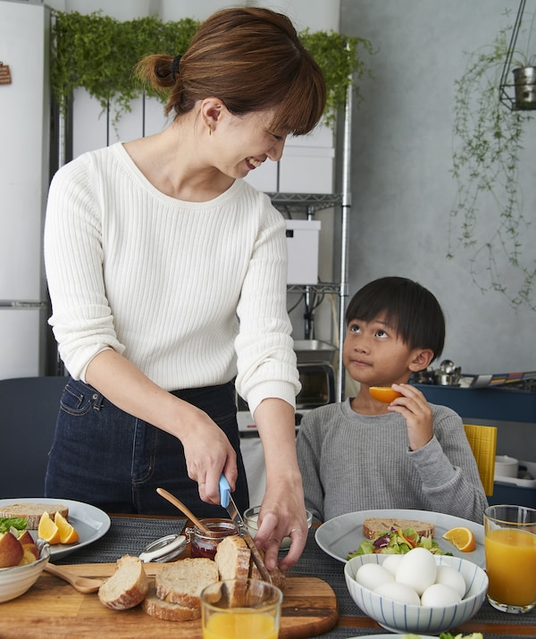 Hiromi and her son preparing breakfast at the table.