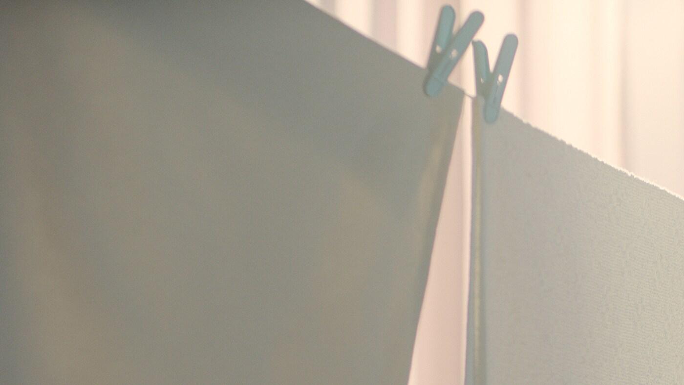 Hiru ehun zuri eta kolore arrosako bat arroparako barra batean; jertse marroi bat soinean daraman pertsona baten besoak eta enborra ikusten dira atzeko planoan.