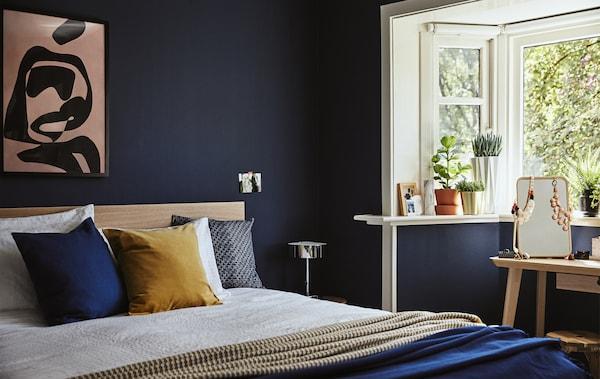 Hjørne av et mørkeblått soverom med dobbeltseng og potteplanter i vinduskarmen.