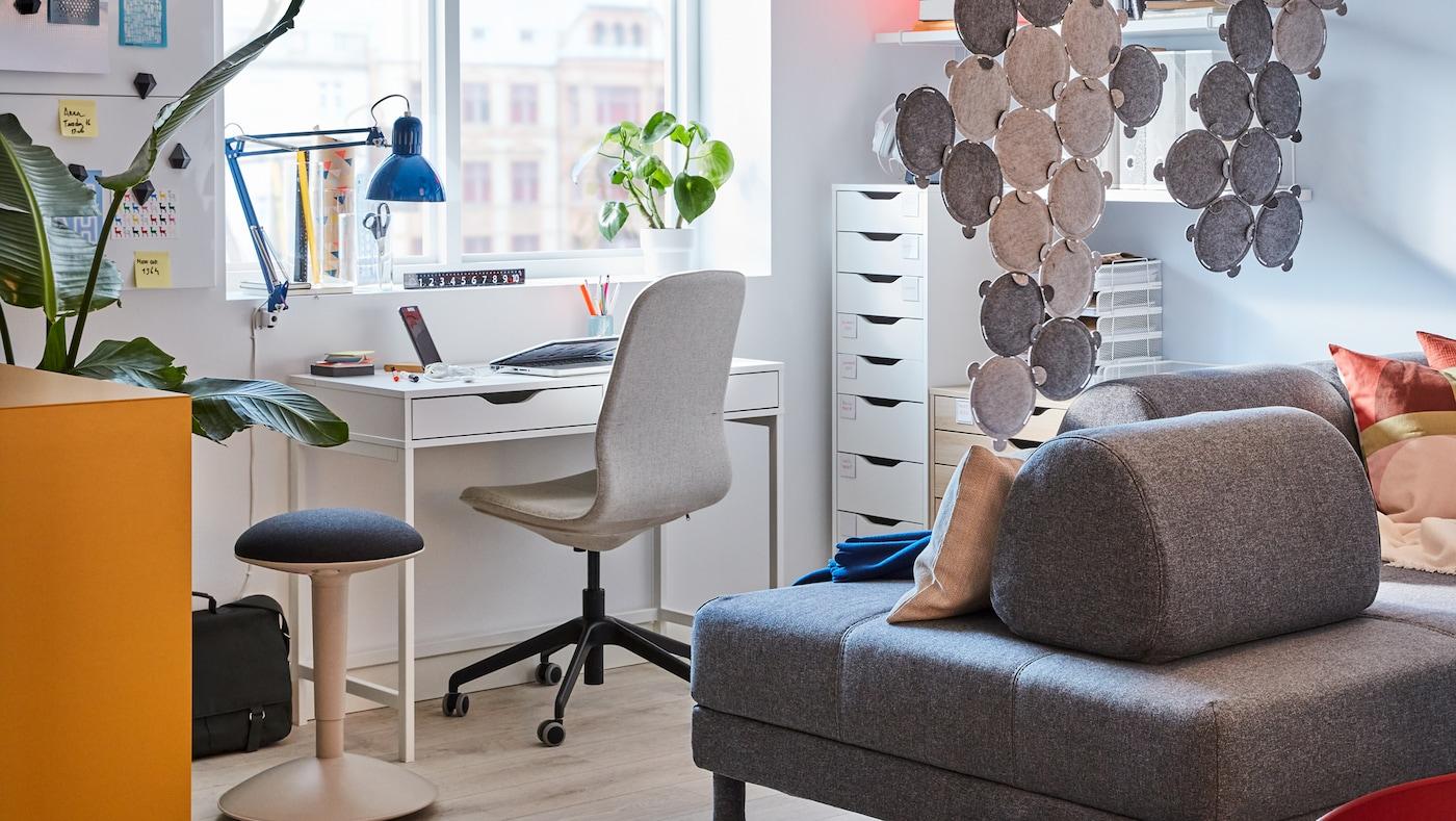 Hjørne med et hjemmekontor i en stue med et hvidt skrivebord med skuffer, en kontorstol og en grå sofa.