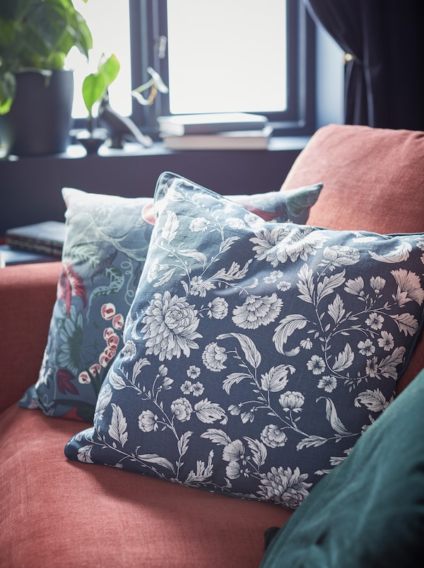 Hjørnet af en rød GRÖNLID sofa med 3 puder i en gruppe: En med IDALINNEA betræk, de andre i lignende farver.