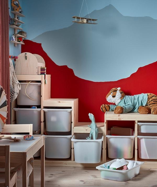 Hjørnet af et børneværelse, hvor en reol med en uregelmæssig form fyldt med legetøj matcher farverne på bagvæggen.