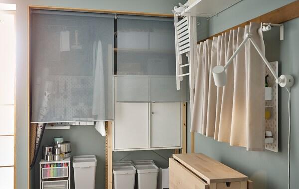 Hjørnet af et rum med hobbytilbehør i IVAR opbevaringselementer bag rullegardiner, et NORDEN bord og hulplader med gardiner foran.