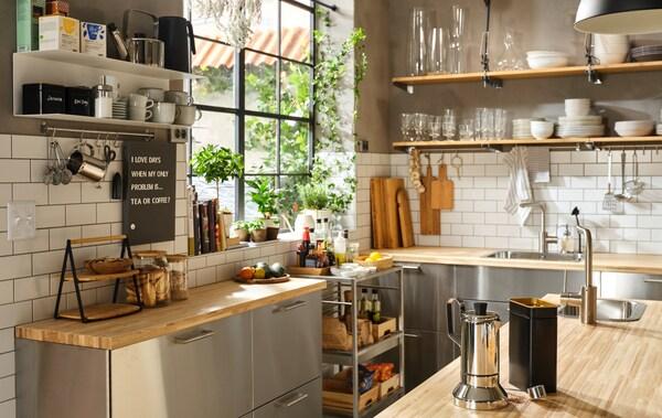 Hjørnet af et stort køkken med et stort vindue, bordplader af træ, fronter af rustfrit stål og åbne hylder til porcelæn.