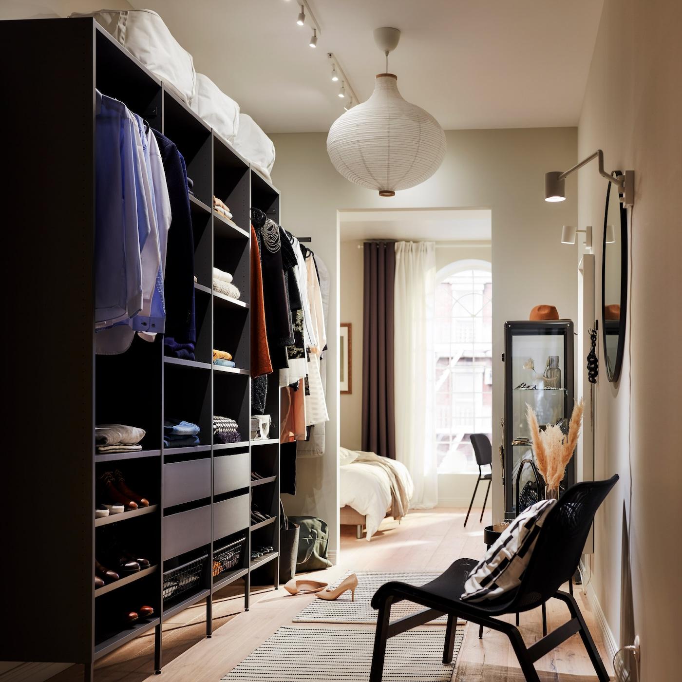 حل دولاب ملابس كبير مفتوح رمادي داكن مع ملابس مطوية على رفوف، وملابس معلقة على سكك تعليق ملابس وأربعة أدراج.