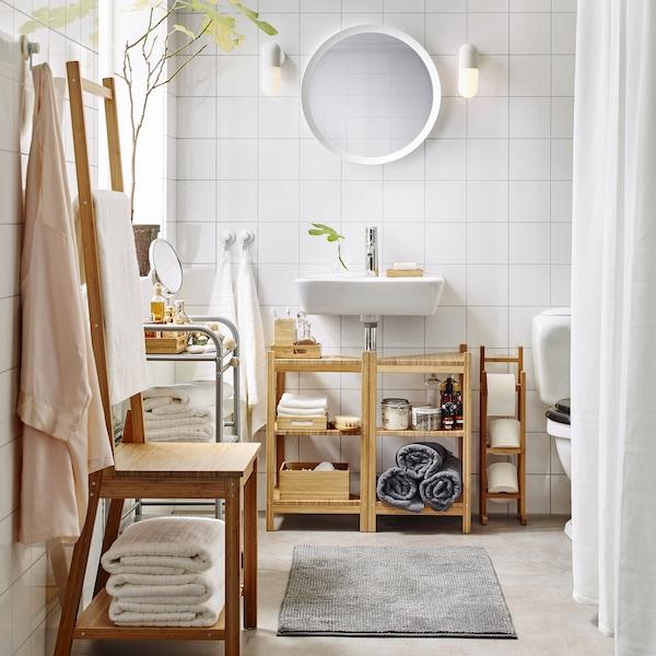حمام أبيض متوسط الحجم به حامل لفافات ورق تواليت، ورفوف، وكرسي علاقة مناشف، كلها مصنوعة من الخيزران.