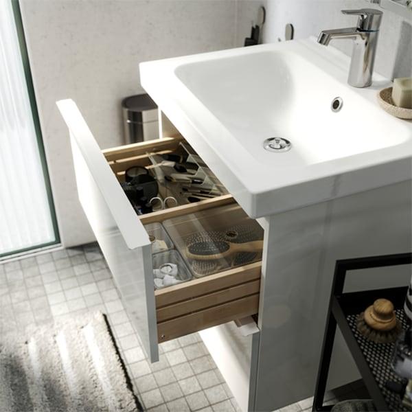 حمام أبيض/رمادي، مع درج مغسلة الحمام مفتوحًا مع صناديق داكنة بالداخل للمساعدة في تنظيم مستلزمات الحمام.