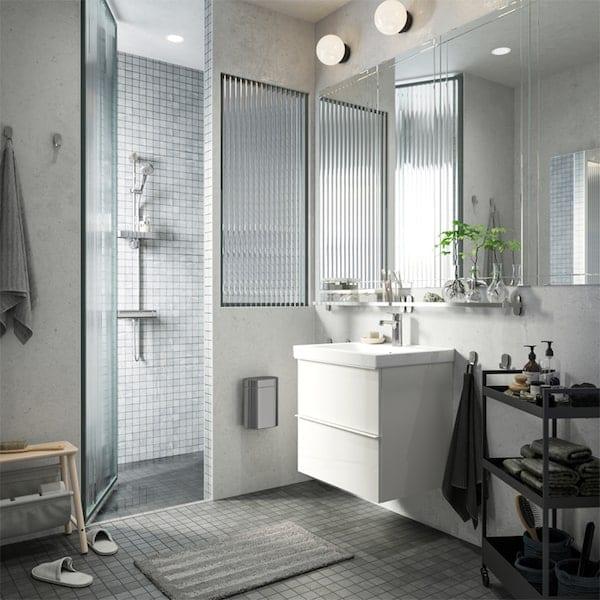 حمام أبيض ورمادي مع دوش وحوض مغسلة أبيض وعربة سوداء عليها مناشف وصابون وغير ذلك الكثير.