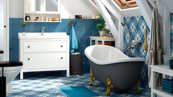 حمام بأرضيةوحوائط بلاطأزرقوحوض استحمام قائم بذاته،ومغسلة بيضاء مع خزائن عاكسة من أعلى.