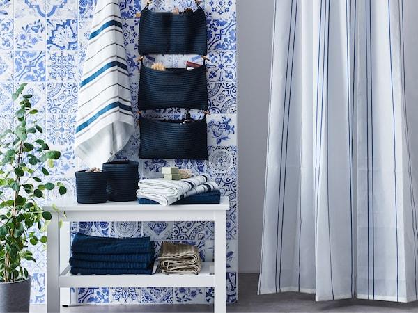حمام به مقعد HEMNES أبيض، وبعض المناشف، وبعض السلات الزرقاء وتخزين معلق مع ستارة دوش.